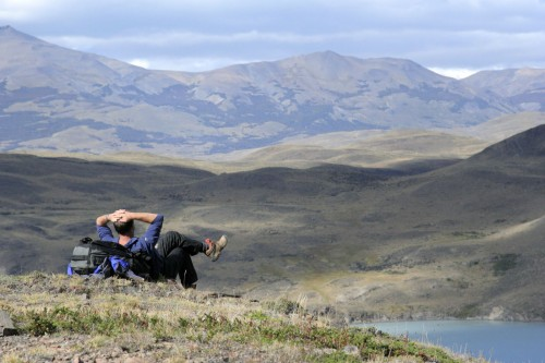 Backpacker relaxing and enjoying the view of the Torres Del Paine national park in Chili